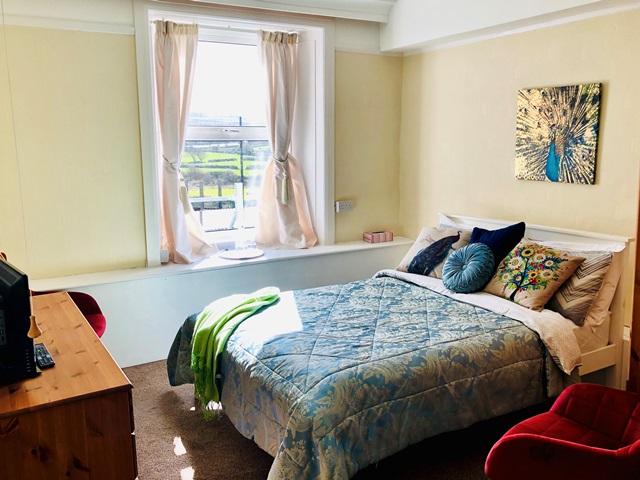 Room 1 bright window beside light blue theme bed